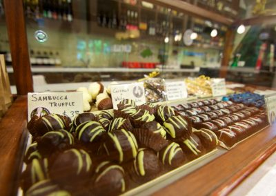 Rows of chocolates behind a glass frame in a cafe.